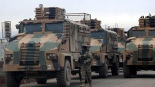 A Turkish soldier walks near Turkish military vehicles in Hazano near Idlib, Syria, February 11, 2020. REUTERS OK